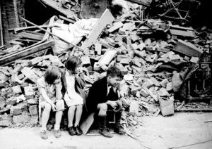 """In 1940, children of an eastern suburb of London, who have been made homeless by the random bombs of the Nazi night raiders, wait outside the wreckage of what was their home."""